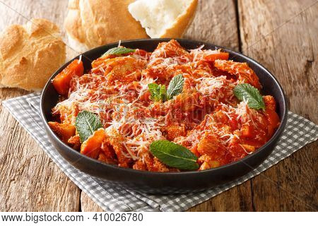 Homemade Braised Tripe In Tomato Sauce With Cheese And Herbs Close-up In A Plate On The Table. Horiz