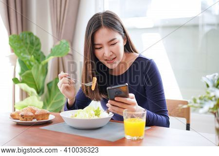 Young Asian Woman Eating Healthy Salad With Fresh Vegetable And Dip The Carrots With A Fork While Lo