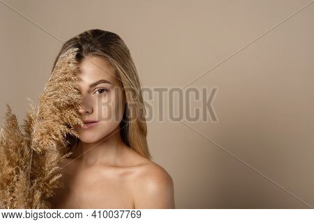 Lovely Young Female Model With Loose Hair Holds Dry Pampas Grass In Her Hands. The Concept Of Natura