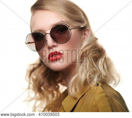 Modern young woman with blonde hair wearing fashionable glasses. Optics, eyewear. Business style. Copy space.