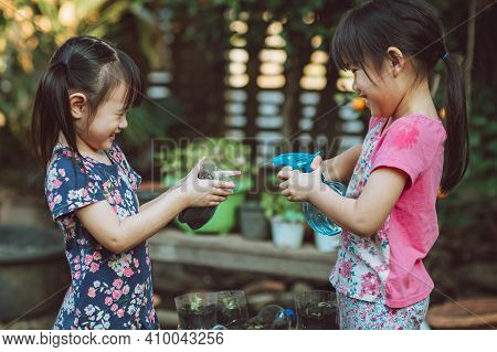 Kids Watering Vegetable Sprout In A Recycled Plastic Reused Bottle. Happy Activity For Children And