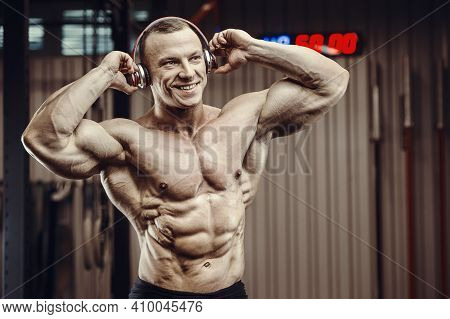 Fitness Man With Headphones At Workout In Gym. Bodybuilding Healthy Concept Background - Muscular Fi