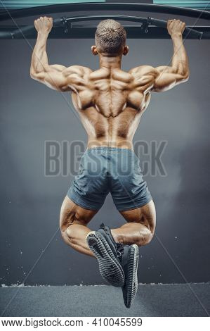 Fitness Man Pumping Up Muscle Doing Pull-ups Exercises In Gym Naked Torso. Handsome Strong Athletic