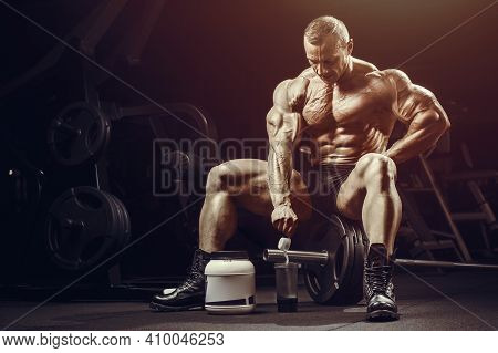 Fitness Man At Workout In Gym With Protein Powder Jar. Bodybuilding And Healthy Lifestyle Concept Ba