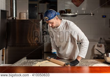 Pizza Boy Kneads Pizza Dough In A Pizzeria Restaurant Kitchen