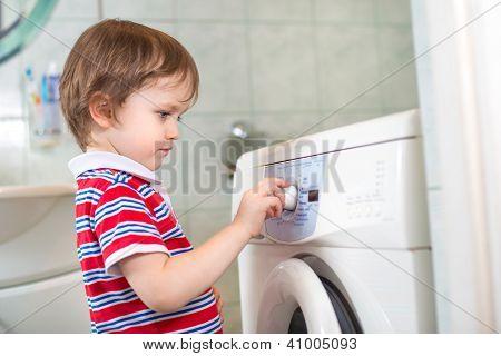 Little Baby Boy Programming Washing Machine In Bathroom