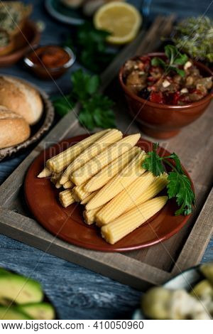 closeup of a plate with some cooked baby sweetcorn on a table, next to a bowl with some escalivada, a side dish made with different roasted vegetables typical of catalonia, spain, and some bread buns
