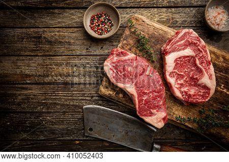 Variety Of Fresh Raw Black Angus Prime Meat Steaks New York, Ribeye And Seasoning On Wooden Backgrou