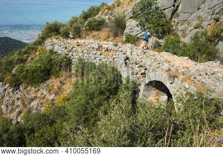Hiking the Lycian Way, Crossing Roman aqueduct bridge, Man tourist walking on ancient ruins on mountain, Trekking in Turkey