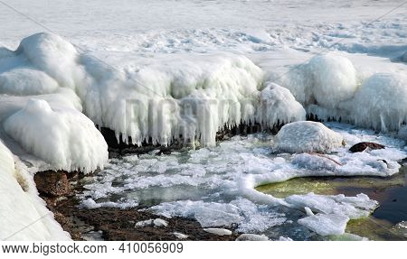 Ice Covered Rocky Coast Of The Baltic Sea On Wintertime In Latvia. White Snow, Ice Covers The Land O