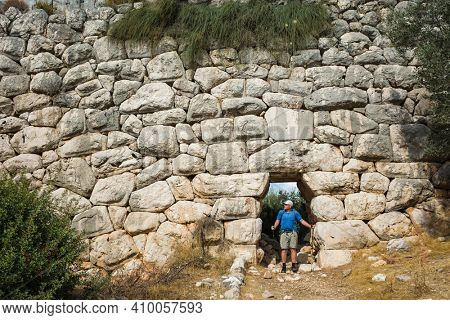 Hiking the Lycian Way. Man is trekking through doorway of Delikkemer Aqueduct, well-preserved polygonal masonry wall, Outdoor activity in Turkey
