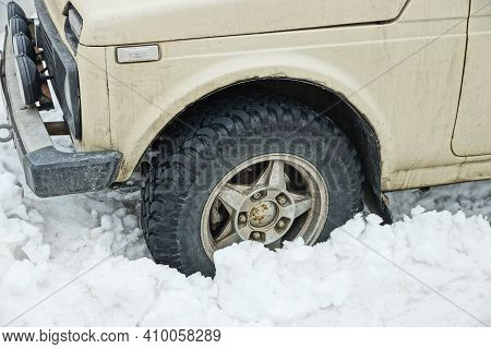 One Black Wheel Of A Gray Car In A White Snowdrift On A Winter Street