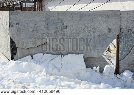Part Of A Gray Broken Slate Fence Wall With Cracks And A Hole In A White Snowdrift On A Winter Stree