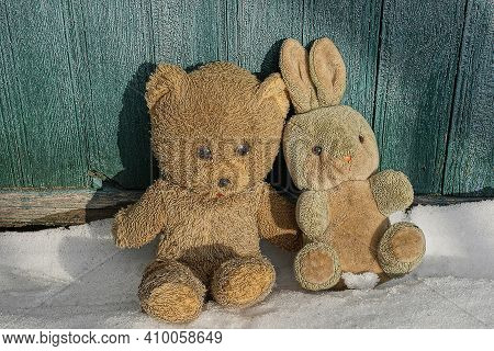Two Old Plush Toys On A White Snowdrift Near A Green Wooden Wall On A Winter Street