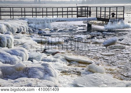 Ice Covered Rocky Coast With An Iron Dock Of The Baltic Sea On Wintertime In Latvia. White Snow, Ice