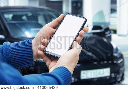 White Screen On A Smartphone In The Hands Of A Man Against The Backdrop Of A Car. Template For A Mob