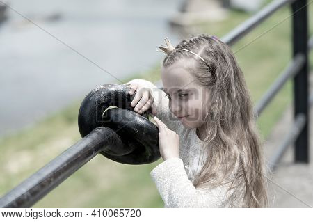 Girl Kid On Smiling Face With Tiny Golden Crown On Head, Riverside Background, Defocused. Princess G