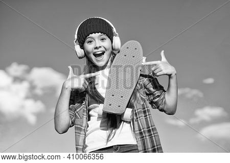 Skateboard You Can Trust. Happy Girl Pointing At Penny Board. Little Skater With Pointing Gesture On