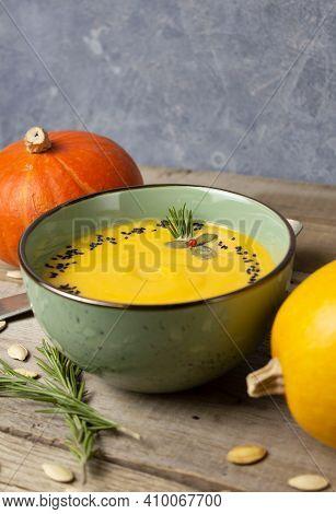 Warming Autumn Cream Pumpkin Soup In A Green Bowl With Copyspace. Pumpkins, Rosemary Twigs, Pumpkin