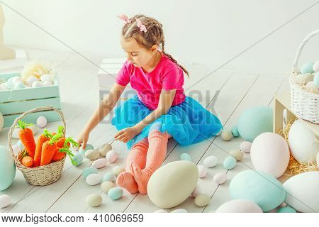 Cute Little Child Girl Wearing Bunny Ears On Easter Day. Girl Sitting With A Basket Of Easter Eggs.