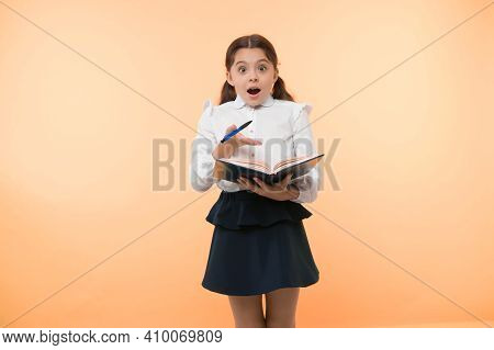 Little Child With Surprised Look. Schoolgirl With Long Hair Hold Book With Pen. Fashion Genius. Back