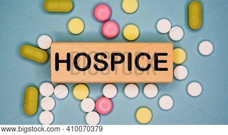 Hospice Written On Wooden Block On A Blue Background Among Multicolored Pills. Medical Concept