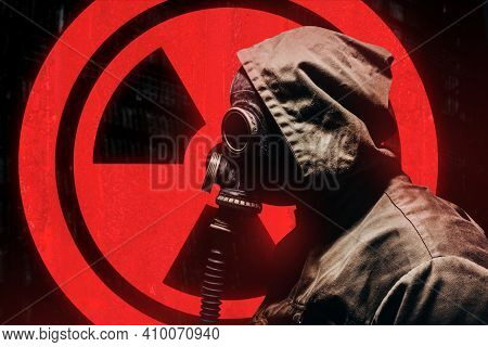 Stalker Warrior In Protective Soviet Gas Mask Standing On Glowing Red Radiation Sign.