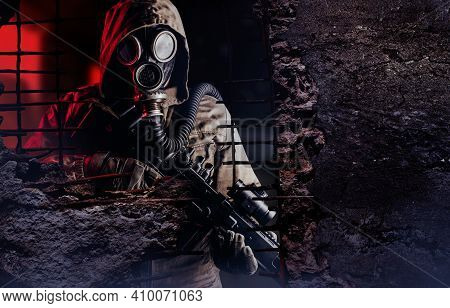 Photo Of A Post Apocalyptic Stalker Soldier In Gas Mask And Rifle Looking Through Destructed Concret