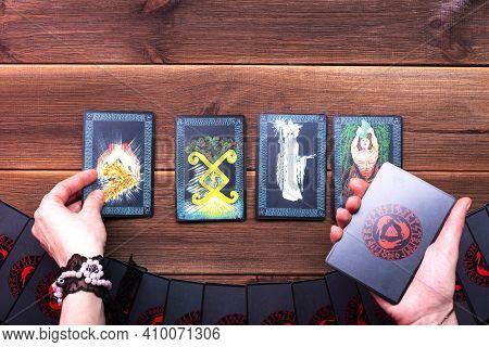Minsk, Belarus, December 27, 2019. Fortuneteller's Hands And Divination Cards On A Wooden Table. Div