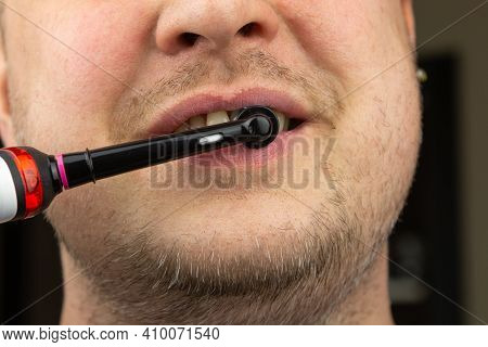 A Man Brushes His Teeth With An Electric Toothbrush. Dental Hygiene For Men