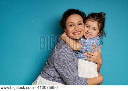 Happy Mother Hugging Her Daughter. Blue Background, Happy Mother's Day Concept, Children Protection