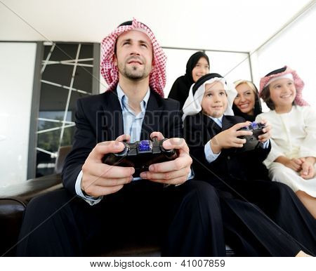 Happy Arabic family playing at home with video game controllers poster