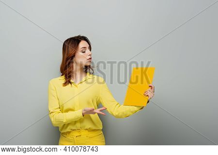 Arrogant Woman In Yellow Blouse Pointing At Notebook On Grey.