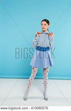 Trendy Woman Touching Bow On Blouse While Looking At Camera On Blue Background