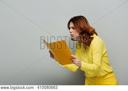 Shocked Woman In Yellow Blouse Staring At Notebook On Grey.