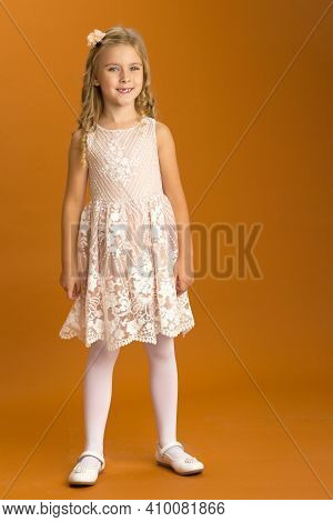 Beautiful Blonde Looking At Camera. An Adorable Seven-year-old Girl With A Serious Expression. Portr