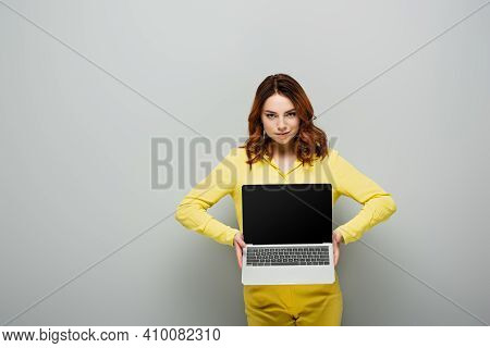 Smirking Woman Looking At Camera While Holding Laptop With Blank Screen On Grey.