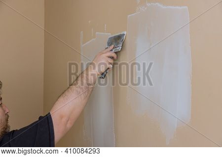 Plasterer Plastering A Wall Of Drywall At A Construction Damaged Wall Repair