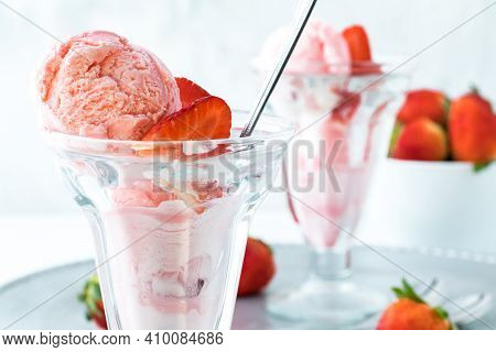 A Close Up Of A Strawberry Ice Cream Sundae With Another One In Behind And A Bowl Of Strawberries.