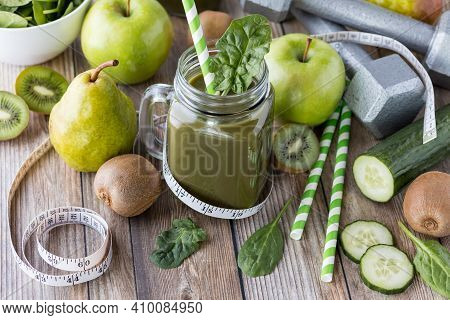 Glass Jar Filled With Green Smoothie Surrounded By Green Fruits And Vegetables. Diet And Weight Loss