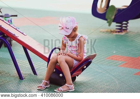 Sad Girl Sits Alone On A Swing In The Playground. Outcast, Loneliness.