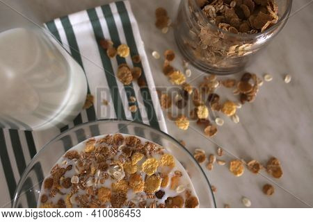 Muesli In A Plate Filled With Milk, Next To It There Is A Glass Bottle Of Milk And A Jar Of Muesli O