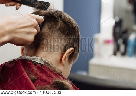 Little Boy Cut With Hairdresser's Machine. Close-up Of Woman Hands Grooming Kid Boy Hair In Barber S