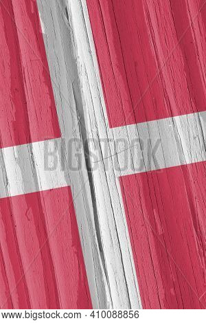 The Flag Of Denmark On A Dry Wooden Surface, Cracked With Age. Light Pale Faded Paint. Vertical Back