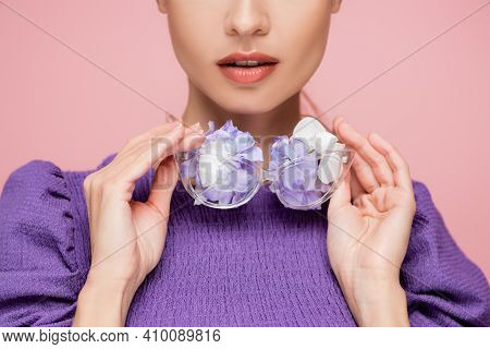 Partial View Of Woman In Purple Blouse Holding Eyeglasses With Flowers Isolated On Pink