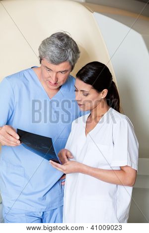Multiethnic radiologic technicians looking at x-ray while standing by MRI scan machine