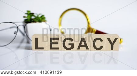 Legacy Concept On Wooden Cubes And Flower ,glasses ,coins And Magnifier On Twhite Background