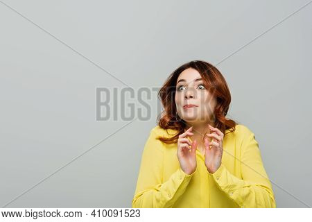 Thrilled Woman Looking Away While Standing With Grabbing Hands Isolated On Grey.