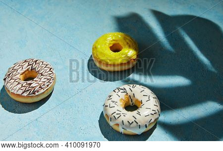 Multicolored Donuts With Frosting, Sprinkles With Shadow From Monstera Leaf On Blue Background