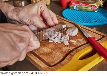 Cooking At Home In The Kitchen According To Recipe From The Internet. Woman Cuts Mini Onions To Make